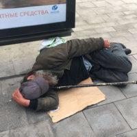Фото бездомного, лежащего на картоне на улице